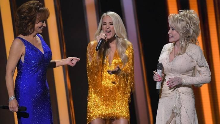 Carrie Underwood (mitte) zusammen mit Reba McEntire (links) und Dolly Parton (rechts) auf der Bühne bei den  53. Country Music Association Awards (CMA) im letzten November: Underwood gibt nun die Moderation des Anlasses ab - zumindest für einige Zeit. (Archivbild)