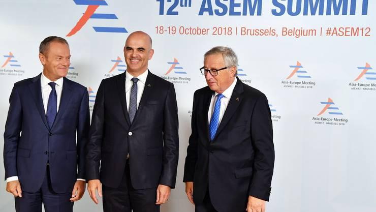 18. Oktober 2018, Brüssel: Bundespräsident Alain Berset wird von EU-Präsident Jean-Claude Juncker (rechts) und von Donald Tusk (links), Präsident des Europäischen Rats, am Asien-Europa-Meeting (Asem) willkommen geheissen.