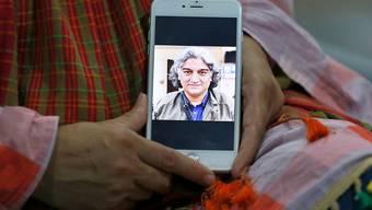 Kaneez Sughra, Ehefrau des verschleppten prominenten pakistanischen Journalisten Matiullah Jan, zeigt Journalisten im Haus eines Verwandten auf einem Smartphone ein Bild ihres Mannes. Der militärkritische Journalist ist nach seiner Verschleppung am Dienstag in der pakistanischen Hauptstadt Islamabad wieder frei. Foto: Anjum Naveed/AP/dpa