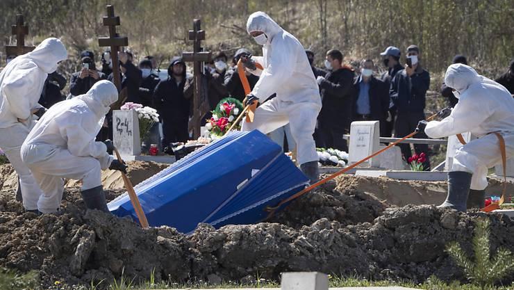 Trotz dramatische Lage sollen die Russinnen und Russen wieder arbeiten: Totengräber mit Schutzanzügen in Kolpino bei St. Petersburg.