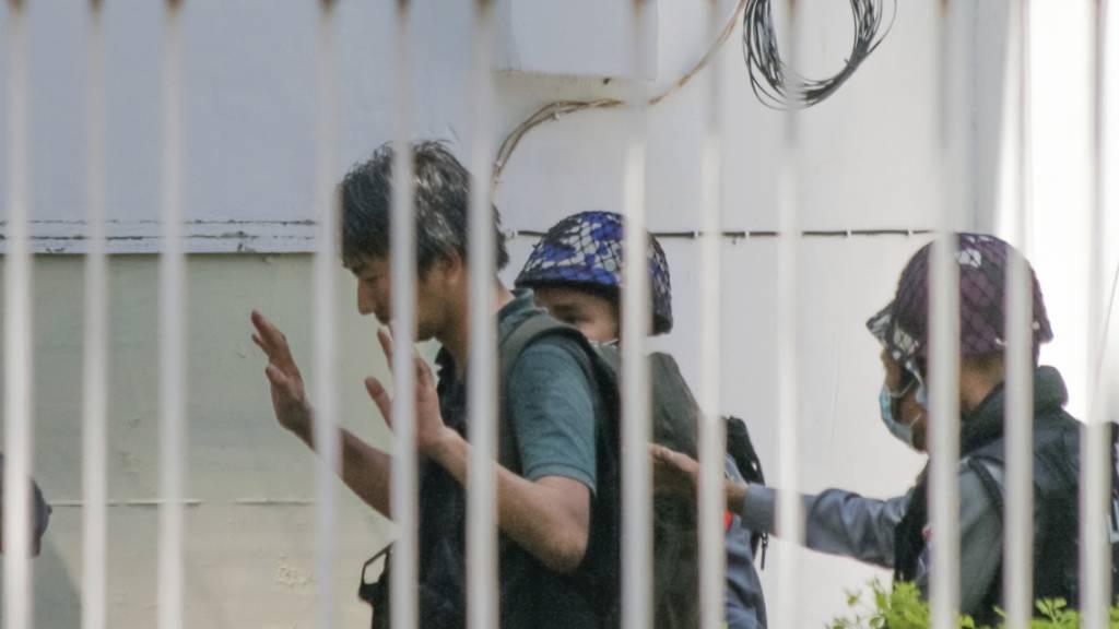 ARCHIV - Yuki Kitazumi (l), Freelance-Reporter aus Japan hebt seine Hände, als er von der Polizei zur Polizeistation Myaynigone eskortiert wird. Der 45-Jährige ist nach Angaben der japanischen Botschaft in das berüchtigte Insein-Gefängnis gebracht worden, in dem viele politische Häftlinge festgehalten werden. Foto: -/AP/dpa