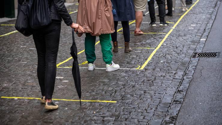 Aufkleber am Boden veranlassen die Einhaltung von Distanz vor einem Geschäft in Zürich.