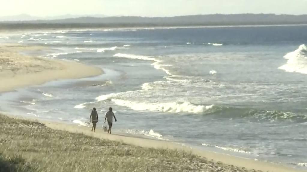 In diesem Standbild aus einem Video gehen Menschen an einem Strand in Tuncurry, Australien entlang.