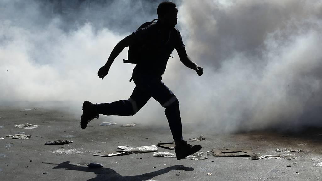 Die Gewalt zwischen Einheimischen und Fremdarbeitern entlädt sich in Südafrika seit mehreren Tagen (im Bild vom 3. September flieht ein Südafrikaner nach Plünderungen in Geschäften Zugewanderter in Johannesburg).