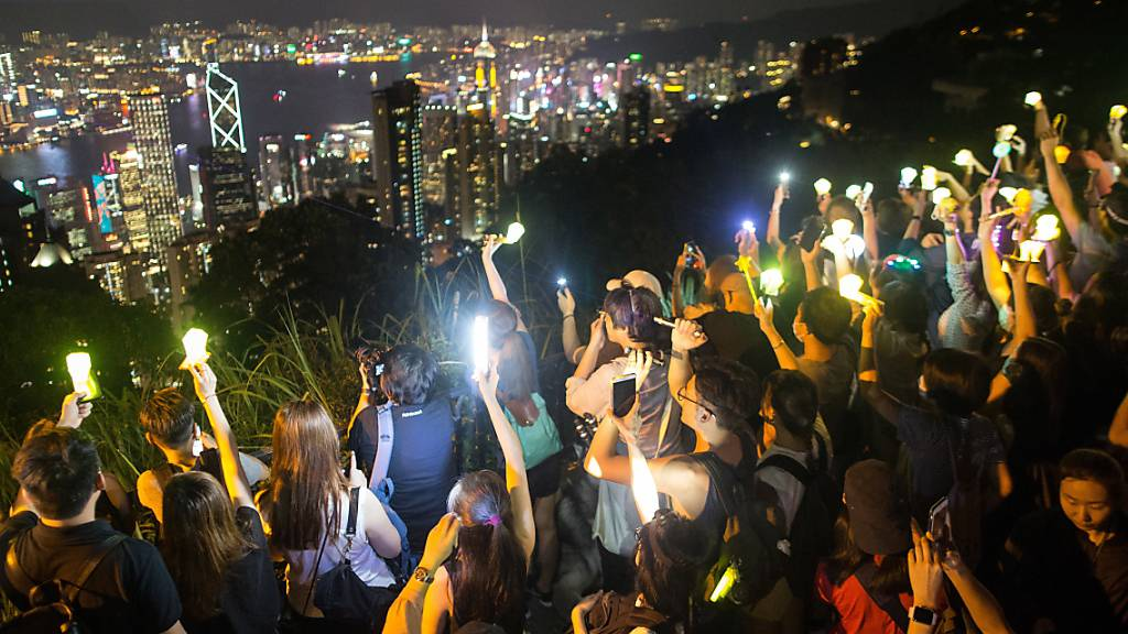 Regierungskritiker in Hongkong bilden am Victoria Peak eine Menschen- und Lichterkette.
