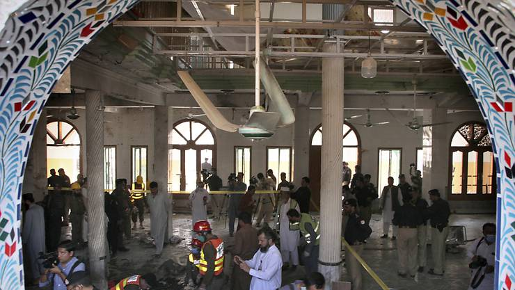 Rettungshelfer und Polizisten inspizieren den Ort in einer Koranschule, in der eine Explosion stattgefunden hat. Dabei sollen auch Kinder getötet und viele weitere Menschen verletzt worden sein. Foto: Muhammad Sajjad/AP/dpa