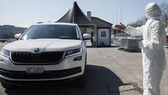 Ein Betreuer des Berner Coronavirus-Testzentrums weist anlässlich einer Besichtigung für Medienschaffende ein Fahrzeug ein.