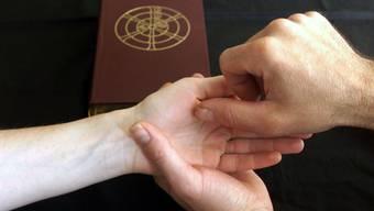 Krankensalbung: Mit geweihtem Öl zeichnet der Priester ein Kreuzzeichen auf die Stirn und auf die Hände des Kranken. (Nadine Loesaus/KNA)