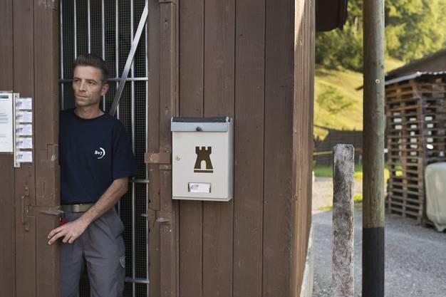Bunkerbesitzer Daniel Miescher öffnet eine hölzerne Schiebetuer, welche das Gittertor vebirgt, das den Eingang zu seinem Artilleriebunker freigibt