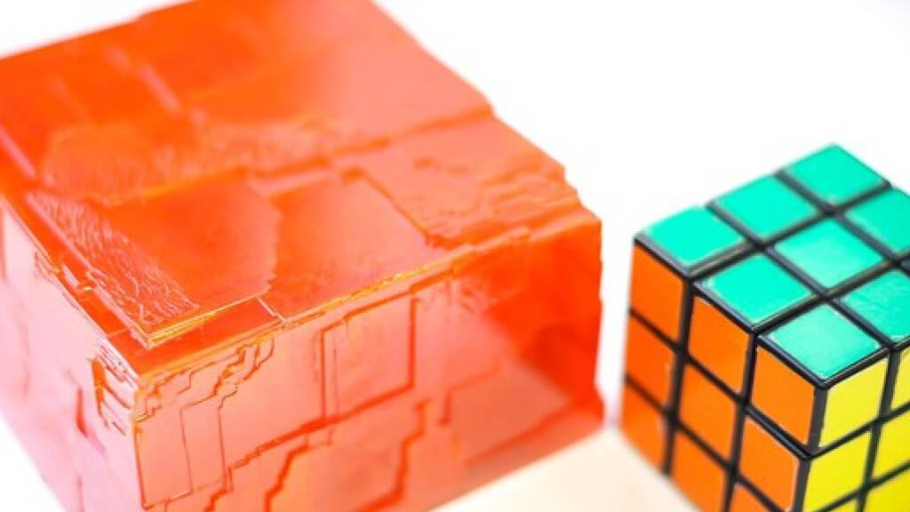 EPFL-Forscher haben einen Perowskit (l neben einem Rubik-Würfel) gezüchtet, der Gammastrahlen entdeckt. Im Unterschied zu bisher bekannten Perowskiten, haben die Forscher den  CH3NH3PbBr3-Kristall zu einem «Mocken» von 3,8 Kilo hochgezüchtet. Das macht ihn fit für die industrielle Herstellung (zVg).