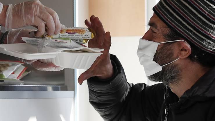dpatopbilder - Ein Freiwilliger reicht einem Obdachlosen mit Mund-Nasen-Schutz Essen. Landesweit in Italien sind verschärfte Corona-Schutzvorschriften in Kraft getreten. Foto: Antonio Calanni/AP/dpa