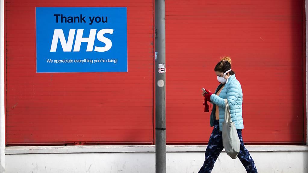 ARCHIV - Eine Frau geht im schottischen Edinburgh an einem Plakat mit der Aufschrift «Thank you NHS» vorbei. Foto: Jane Barlow/PA Wire/dpa