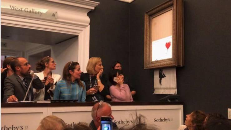 Verdutzte Zuschauer nach Banksys-Schredder-Aktion.