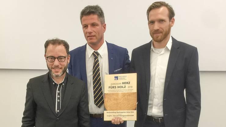 Daniel Wehrli, Präsident Pro Holz Aargau, ehrt die Vertreter der Bauherrschaft Graphis für die beispielhafte Anwendung des ökologischen Werkstoffes Holz.