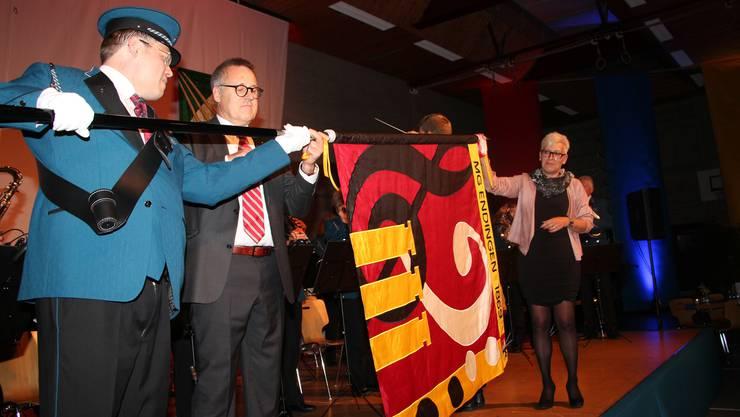 Karin Werder und Lukas Keller präsentieren, assistiert von Fähnrich und OK-Präsident Peter Fäs, die neue Fahne.