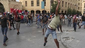 Demonstranten werfen bei einem regierungskritischen Protest in der Nähe des Parlamentsplatzes in Beirut Steine in Richtung der Bereitschaftspolizei. Foto: Bilal Hussein/AP/dpa