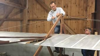 Thomas Fessler (links) arbeitet zusammen mit Markus Müller an der Restaurierung des historischen Hängegleiters.