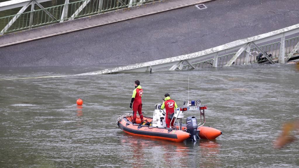 Rettungskräfte suchen im Bereich der eingestürzten Brücke nach Vermissten.