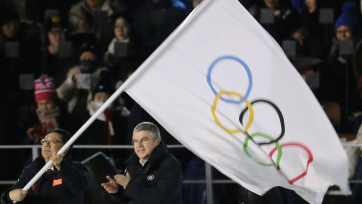 Chen Jining, der Stadtpräsident von Peking, schwenkt vor den Augen von IOC-Präsident Thomas Bach die olympische Flagge