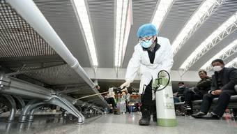 Ein Arbeiter desinfiziert Sitzbänke einer Bahnstation in der chinesischen Stadt Nanchang.