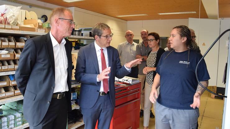Geschäftsinhaber Friedrich Schütz (l.) und Regierungsrat Urs Hofmann unterhalten sich mit Riana Häberli, früher Coiffeuse, heute Automatikmonteurin.