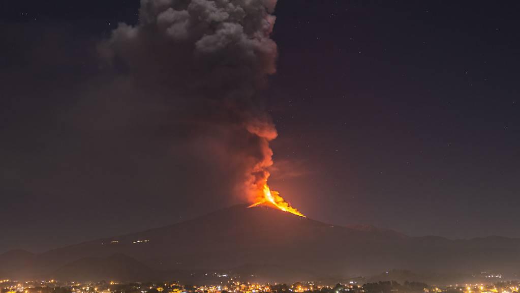 Flammen und Rauch steigen aus dem Vulkans Ätna auf und überragen die Stadt Pedara auf Sizilien.