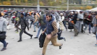 Flüchtlinge überqueren Absperrungen im Sammelzentrum an der Slowenisch-Österreichischen Grenze