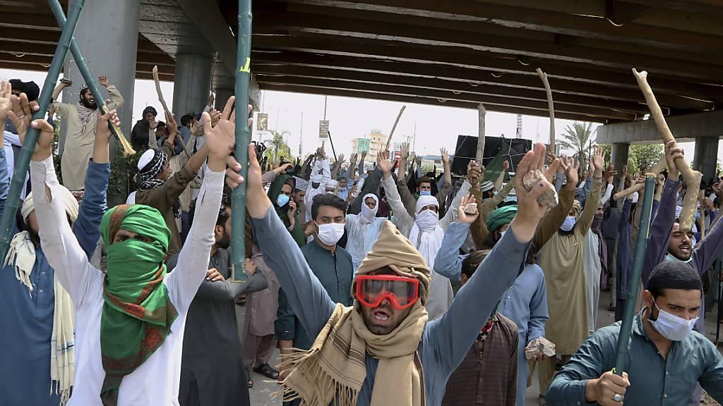 Anhänger von TLP-Parteiführer Rizvi halten während eines Protests Bambusstöcke und Steine in die Höhe. Foto: Muhammad Sajjad/AP/dpa