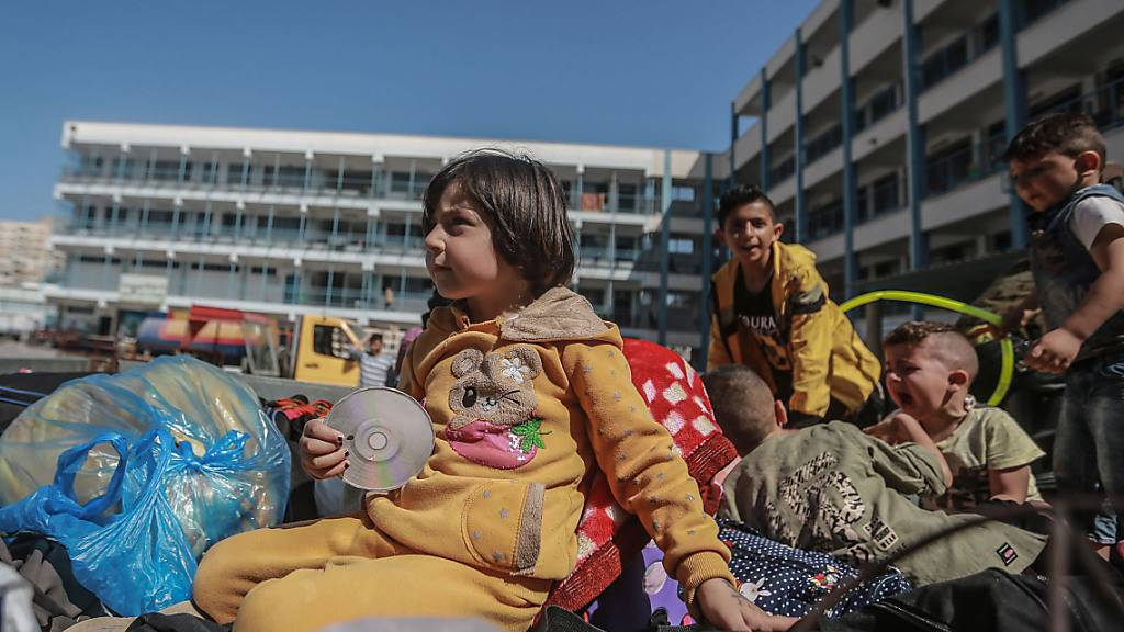 Palästinenser sitzen mit ihren Habseligkeiten vor einer UN-Schule, in der sie Schutz suchen. Sie mussten während der israelischen Luftangriffe aus ihren Häusern fliehen inmitten des eskalierenden Aufflammens der israelisch-palästinensischen Gewalt. Foto: Mohammed Talatene/dpa