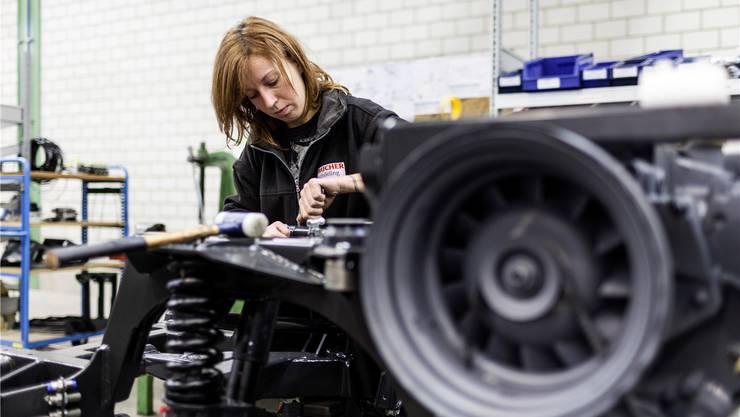 Eine Angestellte von Bucher Municipal schraubt in der Fabrik in Niederweningen Fahrzeugteile zusammen.