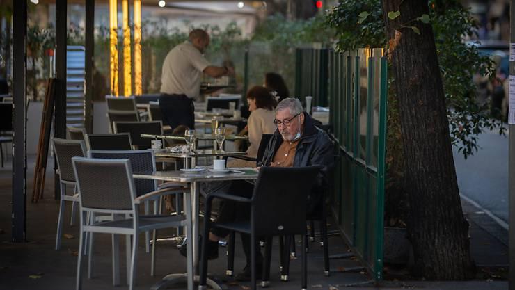 Ein Mann liest auf der Terrasse eines Cafés in Barcelona. Foto: David Zorrakino/EUROPA PRESS/dpa