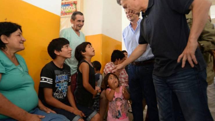 Argentiniens neugewählter Präsident Mauricio Macri bei Flutopfern. Sein Gehalt spendet er künftig für eine Suppenküche.