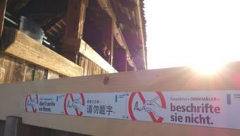 Neue Schilder an der Kapellbrücke in der Stadt Luzern fordern seit Mittwoch Passanten auf, Kritzeleien auf dem Wahrzeichen zu unterlassen.