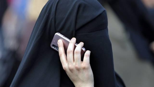 Eine vollständig verhüllte Frau telefoniert mit dem Handy (Symbolbild)