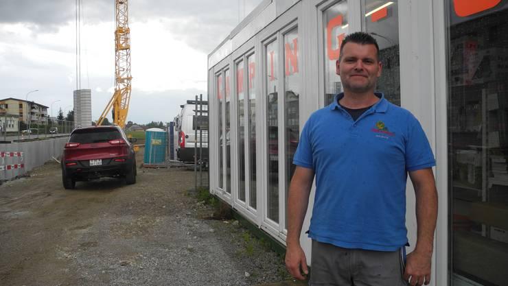 Jan Jäger vor dem provisorischen Camping-Shop. Im Hintergrund entstehen die Neubauten.