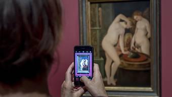 """Eine Besucherin vor dem """"Frauenbad mit Spiegel"""" (1600) von Hans Baldung, genannt Grien, in der Ausstellung """"Weibsbilder - Eros, Macht, Moral und Tod um 1500"""" im Kunstmuseum in Basel."""