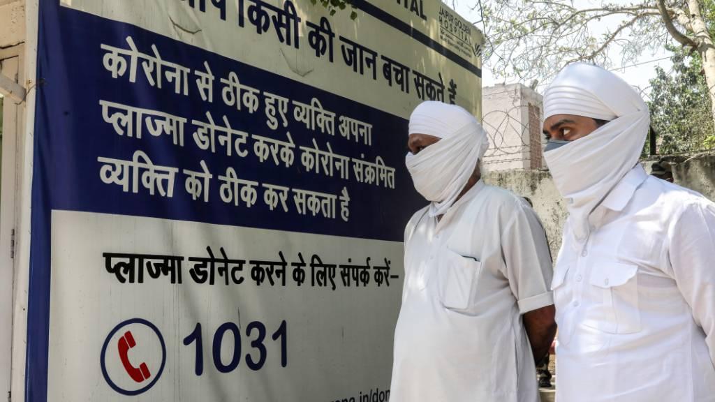 Angehörige von Verstorbenen warten vor dem Jaipur Golden Krankenhaus in Neu Delhi. Foto: Naveen Sharma/SOPA/ZUMA/dpa