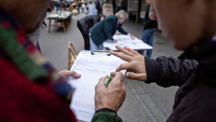 Passanten unterschreiben eine Volksinitiative. (Symbolbild)