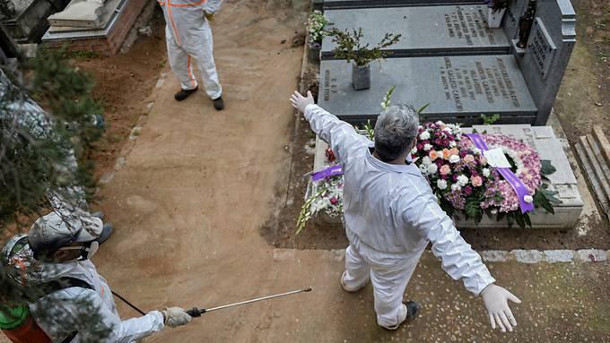 Desinfizieren auf dem Friedhof: Ein städtischer Angestellter desinfiziert einen Kollegen nach einer Beerdigung in Guadalajara.