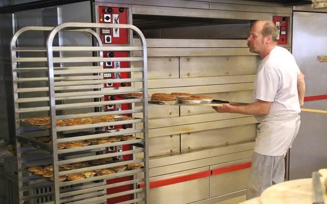 Heinz Wisler nimmt die fertig gebackenen Osterkuchen aus dem Ofen. Jetzt müssen sie erst abkühlen, bevor sie mit Puderzucker dekoriert werden.