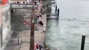 Ein Parkour-Sportler nimmt an der Basler Schifflände Anlauf... und springt mit vollem Schwung in den Rhein.
