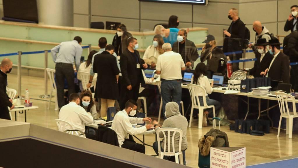 Passagiere des Flugs 232 aus Frankfurt der Fluggesellschaft Arkia Israeli Airlines werden bei der Ankunft am Flughafen Ben Gurion mit elektronischen Armbändern zur Überwachung ausgestattet. Foto: Ilia Yefimovich/dpa