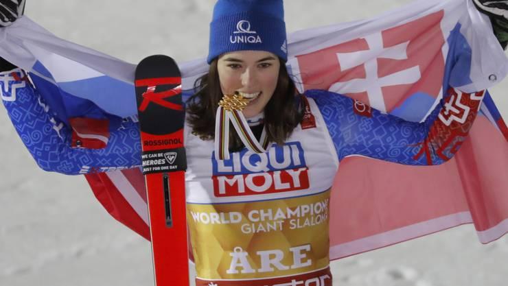 Petra Vlhova, das Gold zwischen den Zähnen, präsentiert sich stolz mit der slowakischen Flagge