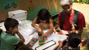 Die Cafébar ist zum Treffpunkt der Bewohner geworden – Jasper Haubensak zeichnet hier mit Kindern. az/archiv