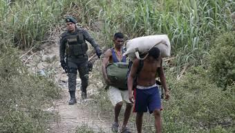 Schmuggel als Versorgungsquelle: Ein kolumbianischer Grenzpolizist begleitet zwei Schmuggler aus Venezuela, die bei La Parade illegal die Grenze überquerten.