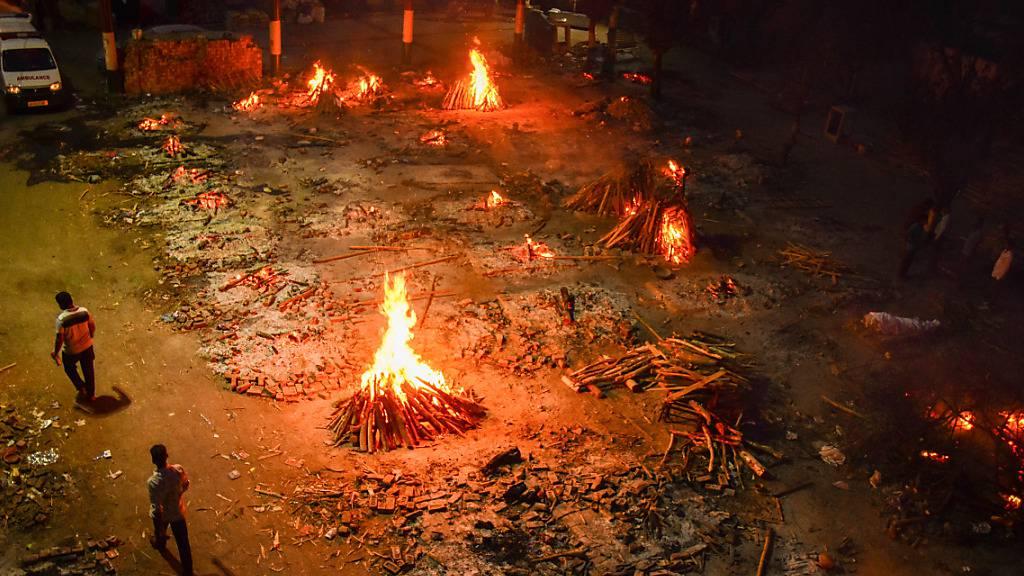 ARCHIV - Zwei Männer gehen vorbei an Holzfeuern auf dem Gelände eines Krematoriums in dem Opfer einer Covid-19 Erkrankung verbrannt werden. Foto: Manish Rajput/SOPA Images via ZUMA Wire/dpa