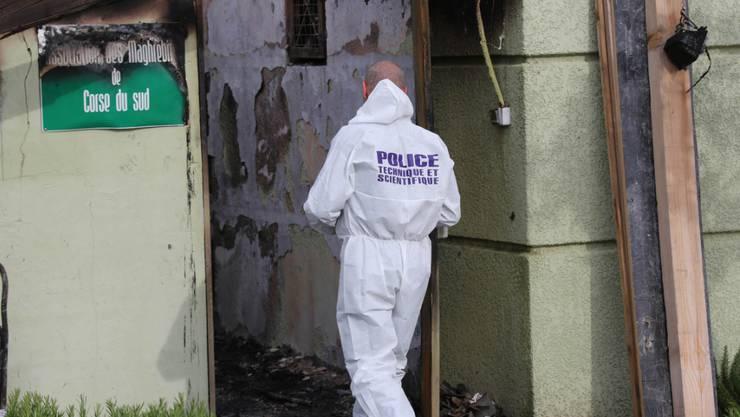Ein Polizist untersucht den vom Feuer beschädigten Gebetsraum in der korsischen Stadt Ajaccio.