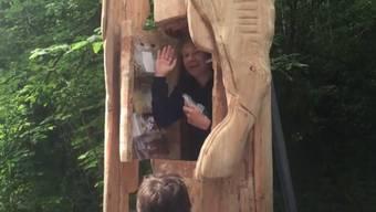 Der Performance-Künstler Abraham Poincheval winkt ein letztes Mal aus der Holzstatue heraus, bevor der Deckel für eine Woche zugeht. Zum Essen hat er Nüsse und Trockenfrüchte dabei. (Screenshot YouTube)