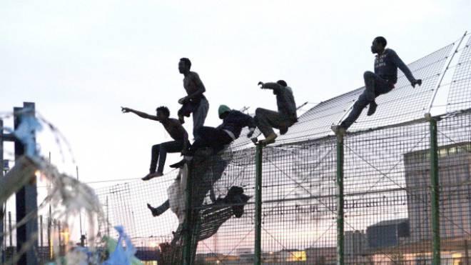Zwölf Kilometer lang, sechs Meter hoch: Flüchtlinge auf dem EU-Grenzzaun im spanischen Melilla. Foto: Keystone