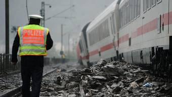 Ein Polizist geht neben dem entgleisten Intercity-Zug der Deutschen Bahn, der im Gleisbett steht
